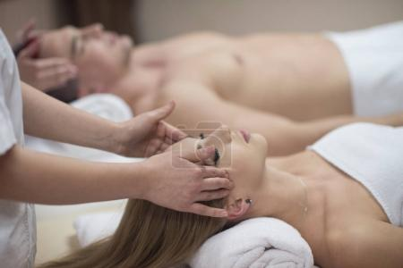 couple enjoying head massage at spa