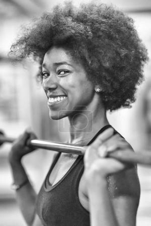 black woman lifting empty bar