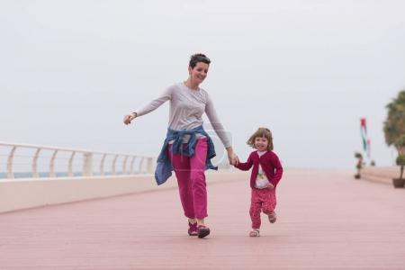 mother and cute little girl on the promenade by the sea