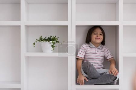 young boy posing on a shelf