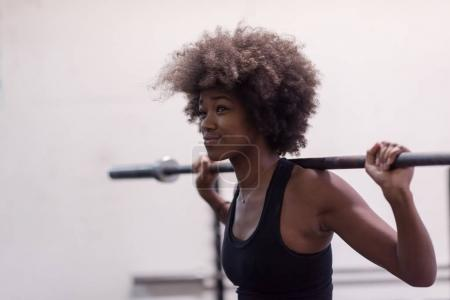 black woman lifting empty bar