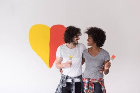 Couple with painted heart on wall
