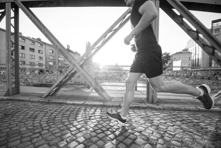young sporty man jogging across the bridge at sunny morning in the city