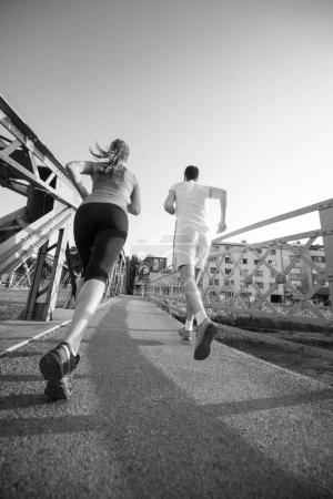 urban sports, healthy young couple jogging across the bridge in the city at sunny morning