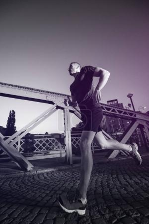 urban sports, young healthy man jogging across the bridge in the city at early morning