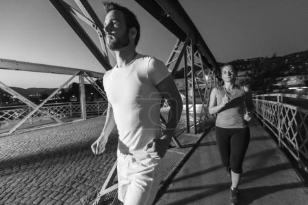 urban sports, healthy couple jogging across the bridge in the city at early morning in night