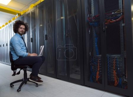 engineer working on a laptop in server room