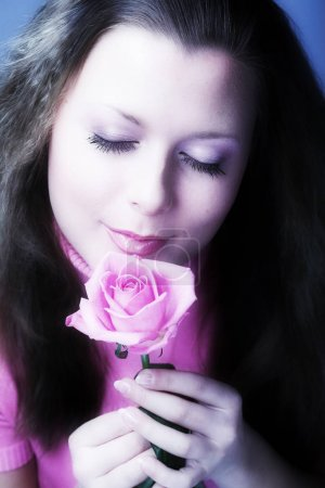 pretty woman holding and smelling pink rose