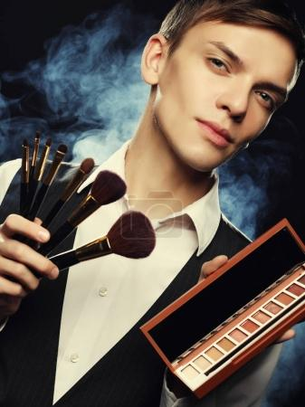 Professional makeup artist posing in studio, holds a palette of