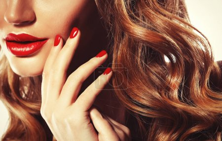 Red Sexy Lips and Nails closeup. Blond hair. Manicure and Makeup