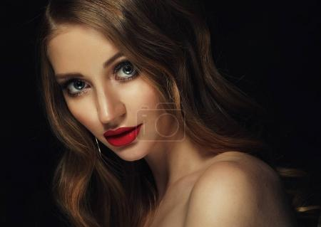 Blonde fashion girl with long and shiny curly hair. Red lips and