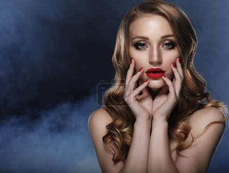Beautiful model girl with long curly hair and red lips. Red mani