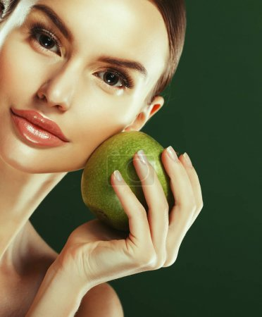 Young woman with  green apple over green background