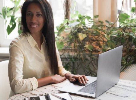 Photo pour Gros plan portrait de souriante jeune femme africaine assise dans un café avec ordinateur portable, concept de style de vie - image libre de droit