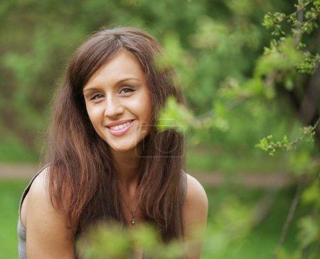 Photo pour Belle jeune femme en robe romantique relaxant dans le jardin - image libre de droit