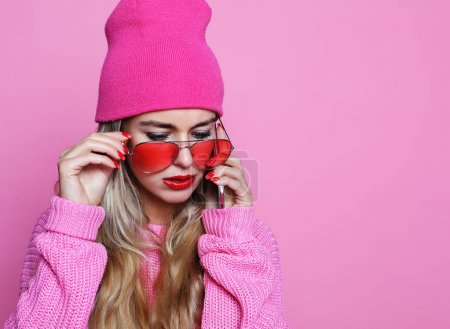 Fashion happy cool smiling girl talking on smartphone in pink clothes