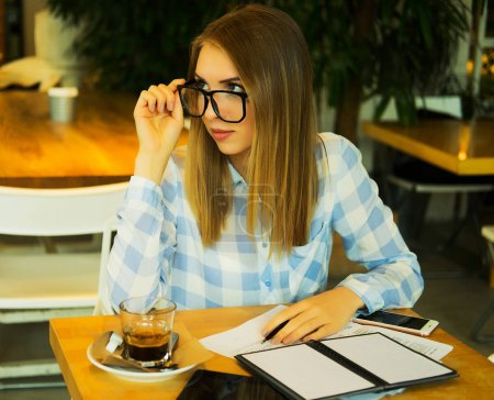 smart woman writing down her ideas and drinking coffe in cafe