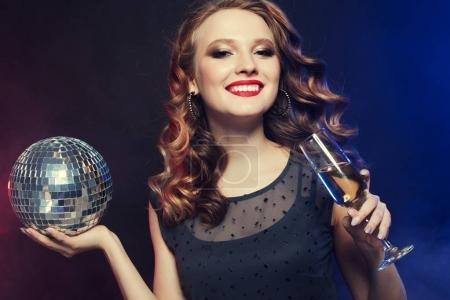 Photo pour Belle jeune femme tenant un verre de vin et un ballon disco à la boîte de nuit - image libre de droit