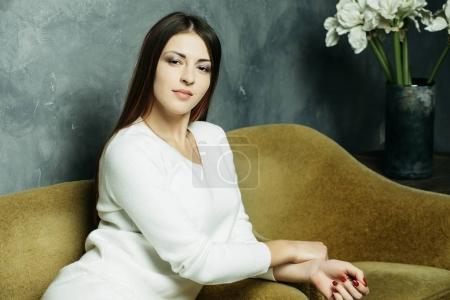Feeling comfortable in her style. Studio shot of beautiful young woman wearing casual outfit  sitting in a big comfortable chair and looking at camera