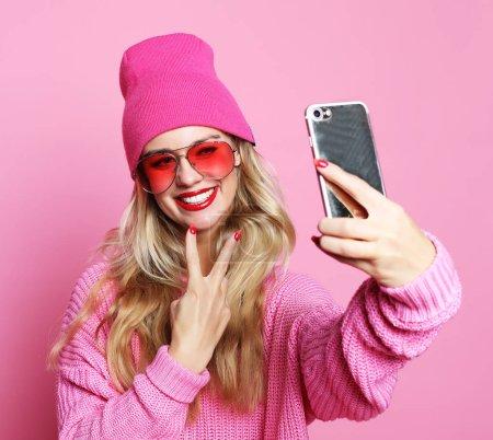 Fashion girl  taking photo makes self portrait on smartphone wea