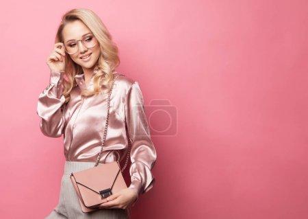 Photo pour Belle femme blonde en chemisier et pantalon portant des lunettes, tenant un sac à main posant sur fond rose. Mode printemps été photo. - image libre de droit