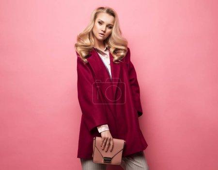 Photo pour Concept mode, people et mode de vie: manteau de Cachemire de belle femme longs bouclés cheveux blonds usure et portefeuille sac à main. Shoot Studio. - image libre de droit