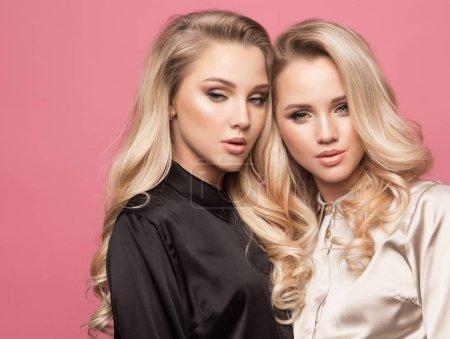 Deux belles jeunes femmes dans des vêtements décontractés, posant sur fond rose