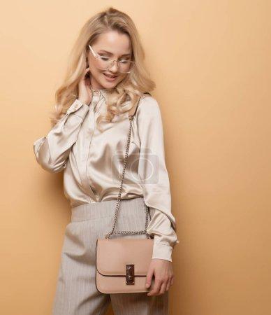 Élégante femme blonde en blouse et pantalon posant sur fond beige