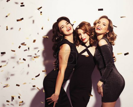 Photo for Attractive girls, cheerful best friends dancing, having fun on party. Wearing  dresses with paillettes, fashionable looking with beautiful wavy hair. - Royalty Free Image