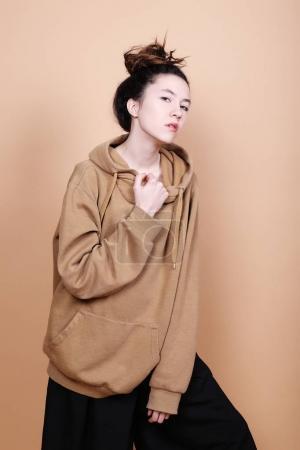 Foto de Concepto de estilo de vida y moda: hermosa mujer morena con ropa casual, posando sobre fondo beige - Imagen libre de derechos