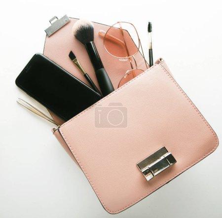 Flache Liege aus rosa Leder Frauentasche offen mit Kosmetika, Zubehör