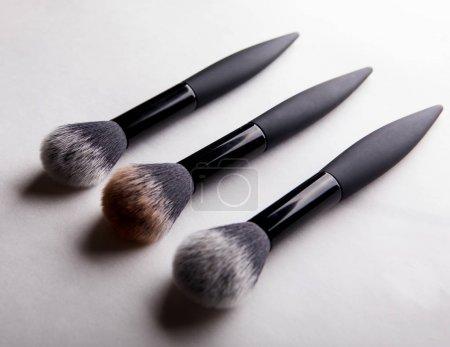 three brushes for powder on white background