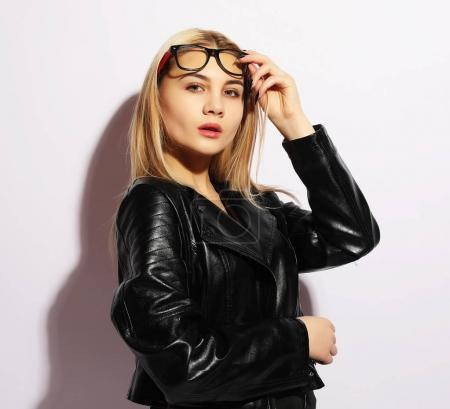 Fashion model in black clothing. Leather jacket and pants, glasses. Street urban minimalist style. Studio shoot.