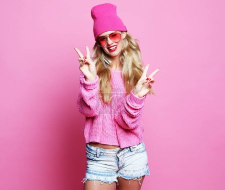 Cool cheerful girl with bright red lips wears modern knitted cap