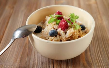 Oatmeal porridge in bowl topped with fresh blueberries and raspb