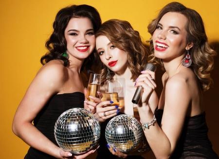 Photo pour Trois joyeux jeunes femmes charmantes avec des boules de disco boire du champagne et s'amuser ensemble sur fond jaune - image libre de droit