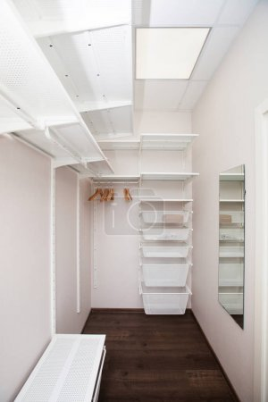 Inside of the empty white walk-in wardrobe