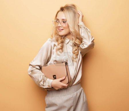 Foto de Mujer rubia elegante blusa y pantalones posando sobre fondo beige. Estilo de la manera. - Imagen libre de derechos