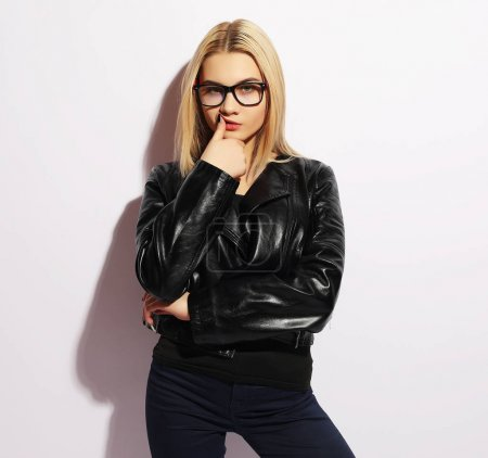 Photo for Fashion portrait of young blond woman. Black leather jacket, pants and glasses. Over white background. Trendy look. - Royalty Free Image