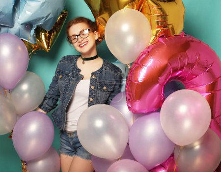 happy redhair girl waiting for party. Gorgeous cheerful young woman having fun with sparkle balloons, over blue background. Lifestyle concept.