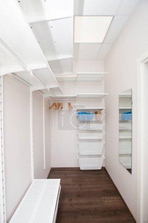Inside of the empty white walk-in wardrobe