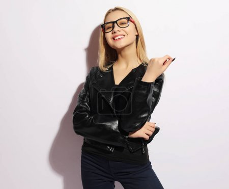 Fashion girl in black clothing. Leather jacket and pants, blank t-shirt and sunglasses. Street urban minimalist style.Studio shoot. Lifestyle.