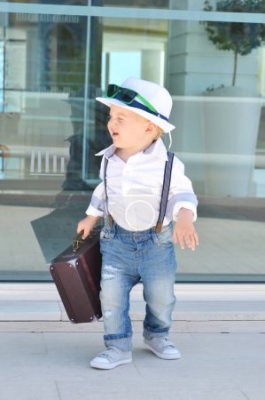 Toddler traveler with a suitcase