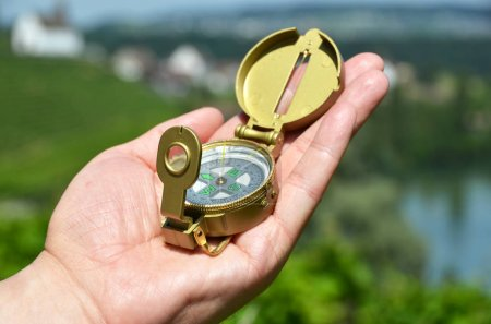 Male hand holding compass