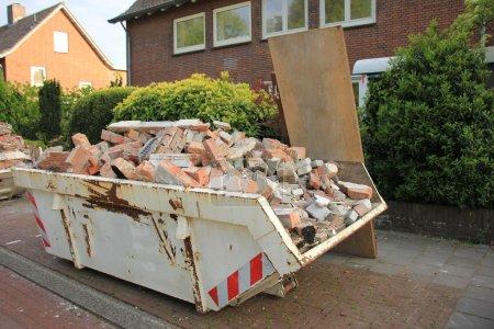 Photo pour Benne à ordures chargée près d'un chantier, rénovation domiciliaire - image libre de droit