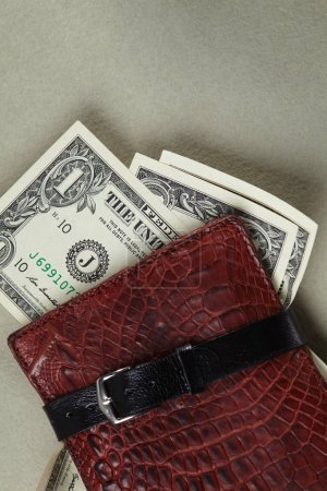 wallet with money wrapped with belt