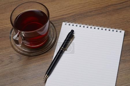 glass cup with tea and notebook