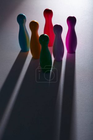 Colorful plastic skittles with shadows on grey background