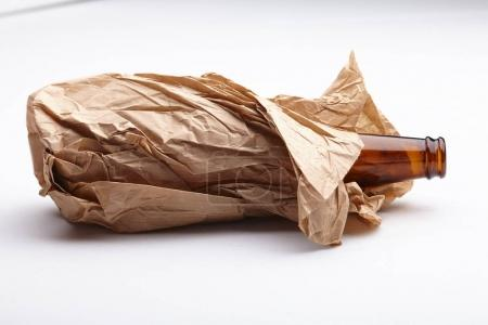 beer bottle in paper bag isolated on white background