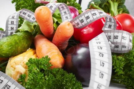 fresh vegetables with measuring tape, close-up